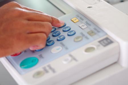 fotocopiadora: Primer dedos presionando botones de la pantalla en la fotocopiadora. Foto de archivo