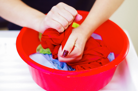 Closeup womans hands handwashing clothes in red plastic washbucket, scrubbing and squeezing fabrics, laundry housework concept. Stock Photo