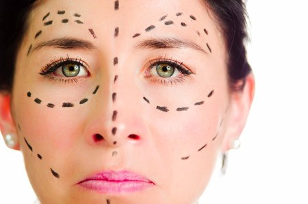 looking into camera: Closeup headshot caucasian woman with dotted lines drawn around face looking into camera, skeptical facial expression, preparing cosmetic surgery. Stock Photo