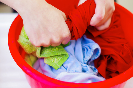 scrubbing: Closeup womans hands handwashing clothes in red plastic washbucket, scrubbing and squeezing fabrics, laundry housework concept. Stock Photo
