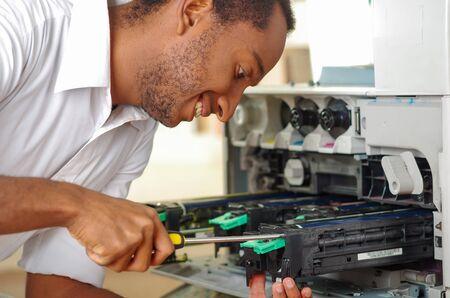 fotocopiadora: El hombre se apoya sobre una fotocopiadora abierta durante las reparaciones de mantenimiento utilizando la herramienta de mano, piezas mecánicas negro. Foto de archivo