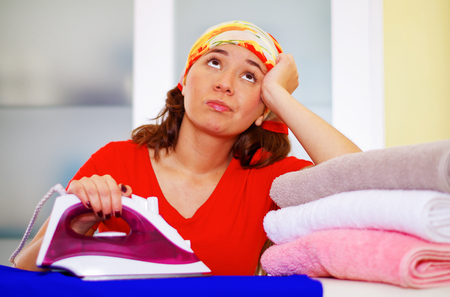 Young charming woman wearing colorful headscarf ironing clothes while daydreaming looking into unknown, laundry housework concept. Stock Photo