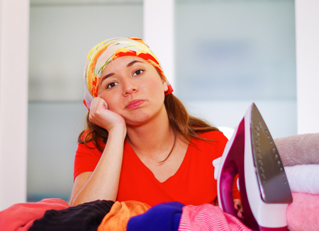 Young charming woman wearing colorful headscarf sitting down in front of ironing device, resting head on her own hand while daydreaming looking into camera, laundry housework concept. Stock Photo