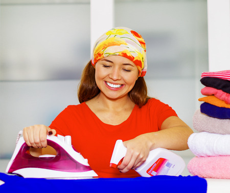 laundry concept: Young charming woman with colorful headscarf ironing stack of clothes while smiling happily, laundry housework concept,