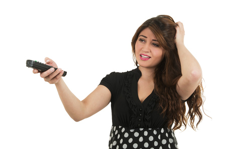unsure: Young pretty girl looking unsure holding remote control isolated on white Stock Photo