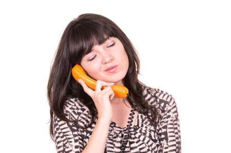beautiful young woman closing her eyes using retro orange telephone  isolated on white