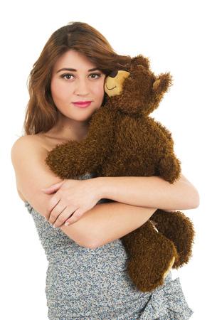 Beautiful brunette teenage girl hugging teddy bear isolated on white