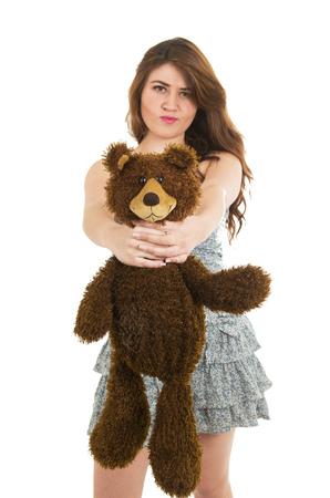 Young pretty angry girl strangling teddy bear isolated on white