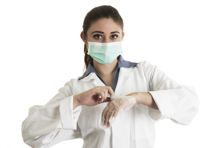Young hispanic female doctor wearing gloves and mask isolated on white Stock Photo