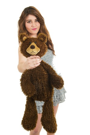 Young pretty unhappy girl strangling teddy bear isolated on white