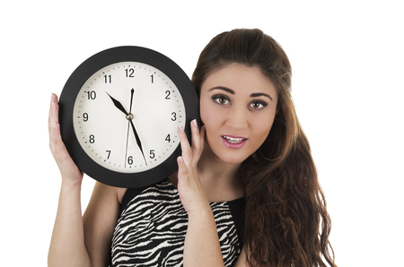 Beautiful young worried woman holding big round clock next to her head isolated on white time concept Stock Photo