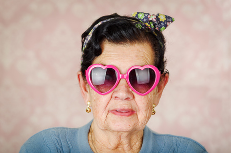 looking into camera: Older cool hispanic woman wearing blue sweater, flower pattern bow on head and pink heartshaped sunglasses looking into camera.
