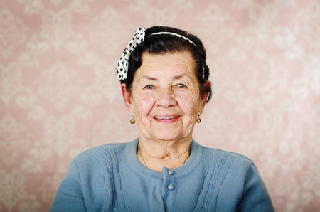 Older cute hispanic woman wearing blue sweater and polka dot bowtie on head smiling happily in front of pink wallpaper. Foto de archivo