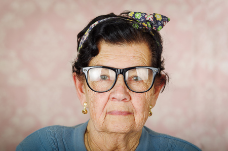 looking into camera: Older hispanic cute woman with flower pattern bow on her head wearing blue sweater and black large framed glasses looking into camera.
