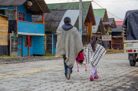 indian artifacts: PASTO, COLOMBIA - JULY 3, 2016: native people with traditional clothes walking in the street in la cocha lake.