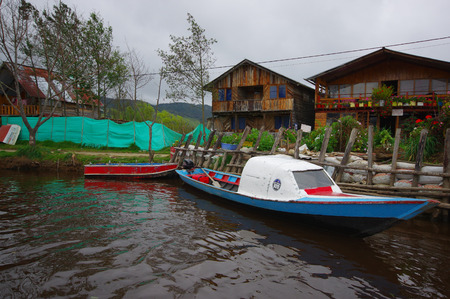 water scape: PASTO, COLOMBIA - JULY 3, 2016: small boats parked next to a shore with some wood houses as background.