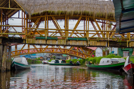 PASTO, COLOMBIA - JULY 3, 2016: some wood bridges standing over some boats on a river close to la cocha lake. Editorial