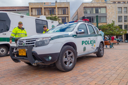enforce: PASTO, COLOMBIA - JULY 3, 2016: unidentified police officers standing next to a police car parked on the central square of the city.