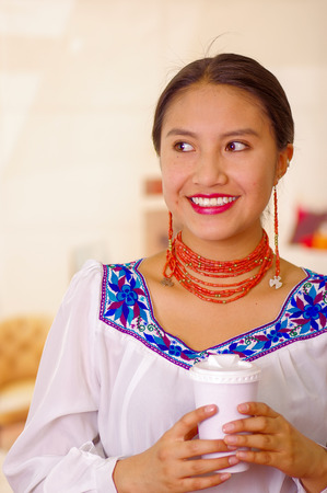 facing on camera: Headshot pretty young woman wearing traditional andean blouse, holding white coffee mug, facing camera, beautiful smile.
