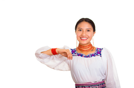 Beautiful young woman standing wearing traditional andean blouse and red necklace, interacting holding out arms smiling happily, white studio background.