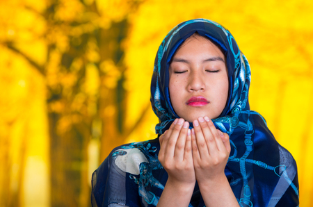 folding camera: Beautiful young muslim woman wearing blue colored hijab, facing camera folding hands performing muslim prayer, autumn forest background.