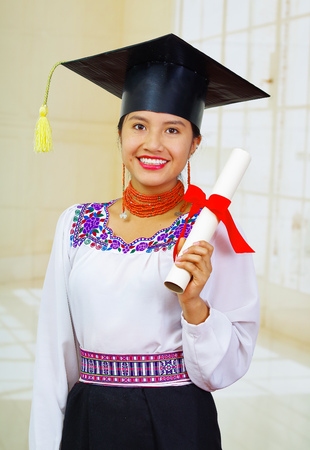 Young female student wearing traditional blouse and graduation hat, holding rolled up diploma, smiling proudly for camera. Stock Photo