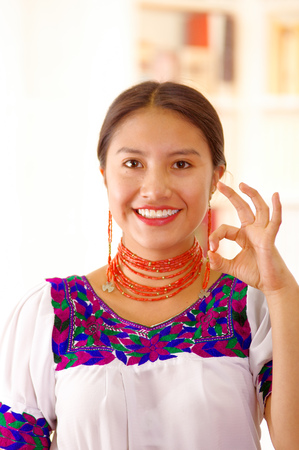 Beautiful young brunette woman wearing traditional andean white blouse with blue decorative edges, facing camera interacting positive, bright household background.