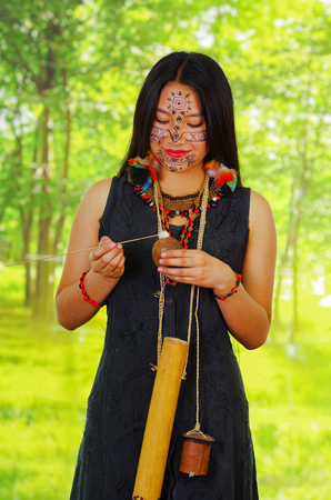 arrow poison: Amazonian exotic woman, facial paint, black dress, case for arrows and small wooden bottle hanging around neck, applying poison to arrow, posing, forest background..