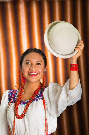 Bautifully dressed hispanic model wearing andean traditional clothing, holding up matching white hat, facing camera smiling, beige studio curtain background.
