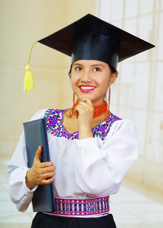 Young female student wearing traditional blouse and graduation hat, holding black diploma booklet while touching chin using hand, thoughtful expression smiling to camera.
