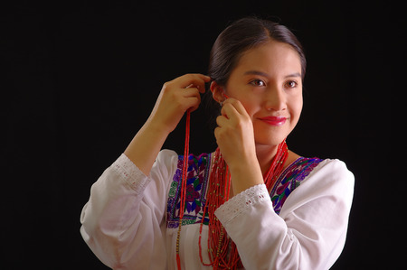 Beautiful young hispanic woman wearing white blouse with traditional embroided edges, attaching red hair extensions herself and smiling, black studio background.