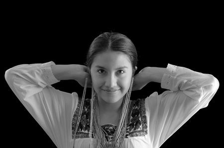 hooking: Beautiful young hispanic woman wearing light colored blouse with traditional embroided edges, attaching typical indigenous necklace herself while smiling, dark studio background, black and white edition.