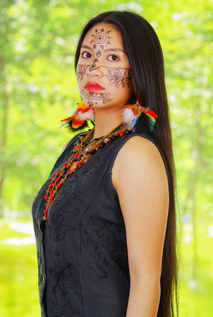 Portrait amazonian exotic woman with facial paint and black dress, posing proudly for camera, forest background..