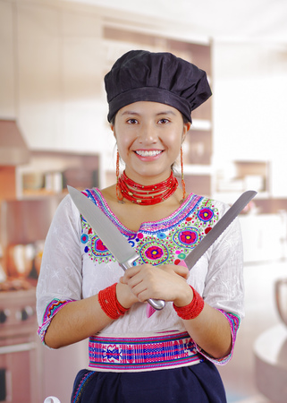 Young woman chef wearing traditional andean blouse, black cooking hat, holding two large knifes, crossing them in front of chest, kitchen background.