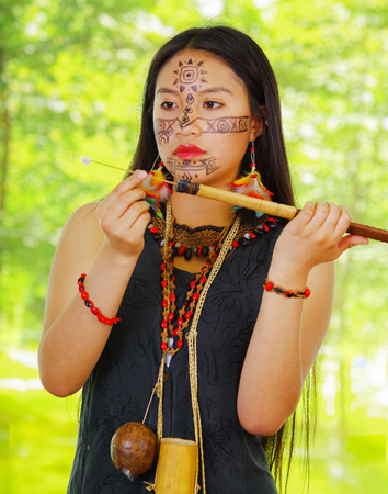 Amazonian exotic woman, facial paint, black dress, case for arrows and small wooden bottle hanging around neck, loading arrow into blowgun, forest background.. Stock Photo