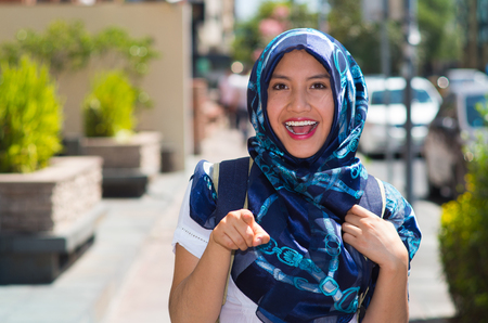 Beautiful young woman wearing blue colored hijab, pointing finger smiling, outdoors urban background. Stock Photo