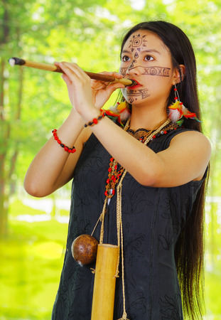 amazonian: Amazonian exotic woman, facial paint, black dress, case for arrows and small wooden bottle hanging around neck, blowing into blowgun, forest background..