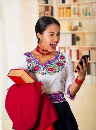 book jacket: Beautiful young lawyer wearing traditional andean blouse with necklace, holding red jacket and book while using mobile phone, looking shocked at screen, bookshelves background.