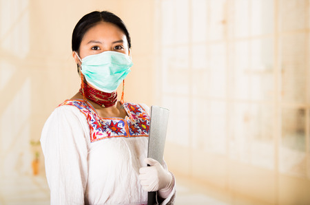 looking into camera: Young beautiful woman dressed in doctors coat and red necklace, face covered with facial mask looking into camera, egg white clinic background.