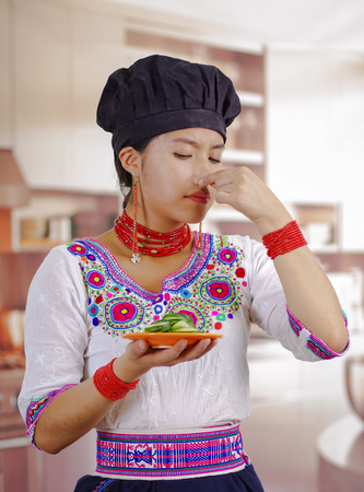 Young woman chef wearing traditional andean blouse, black cooking hat, holding plate of cucumber slices, covering nose for bad smell, skeptic facial expression, kitchen background. Stock Photo