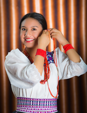 Beautiful hispanic model wearing andean traditional clothing smiling and adjusting decorative hair extension, posing for camera, beige studio curtain background.