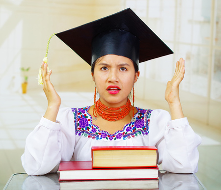 Young female student wearing traditional blouse and graduation hat, sitting by desk with books stacked in front, stressed facial expression. Stock Photo