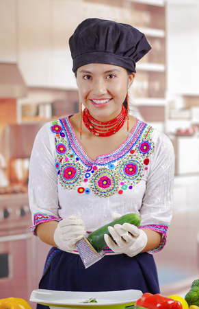 shredding: Young woman chef wearing traditional andean blouse, black cooking hat, vegetables on desk, shredding cucumber into deep plate, kitchen background. Stock Photo