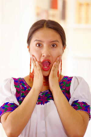 Beautiful young brunette woman wearing traditional andean white blouse with blue decorative edges, facing camera interacting shocked, bright household background.