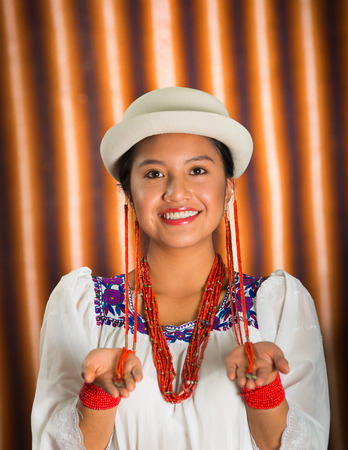 Bautiful hispanic model wearing andean traditional clothing with matching white hat, smiling and interacting using hands for camera, beige studio curtain background.