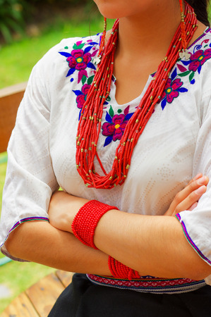ear ring: Closeup beautiful hispanic woman wearing traditional andean white blouse with colorful decoration around neck, matching red necklace, bracelet and ear ring.