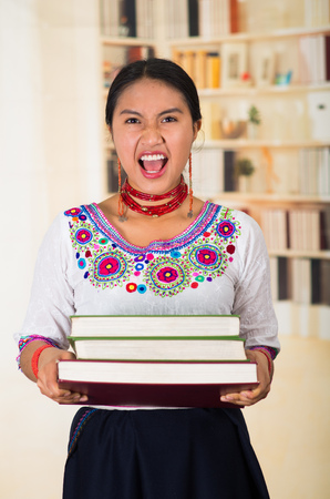 Beautiful young lawyer wearing traditional andean blouse and red necklace, holding stack of books, screaming out to camera, bookshelves background.