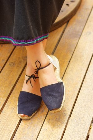 latina america: Closeup womans feet wearing simple traditional andean shoes, lace with knot tied around lower leg, legs crossed.