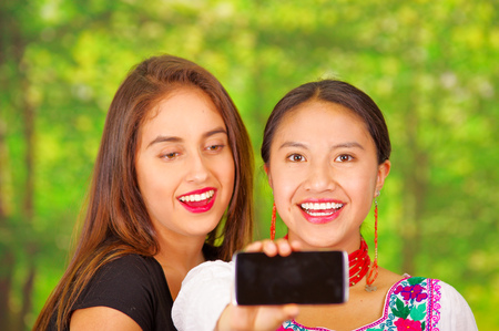facing on camera: Two beautiful young women standing together facing camera, one wearing traditional andean clothing, the other in casual clothes, holding up mobile posing for selfie smiling, park background. Stock Photo