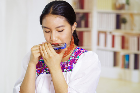 Portrait of young pretty woman wearing beautiful traditional andean clothing, sitting down with while playing the harmonica, bookshelves background.